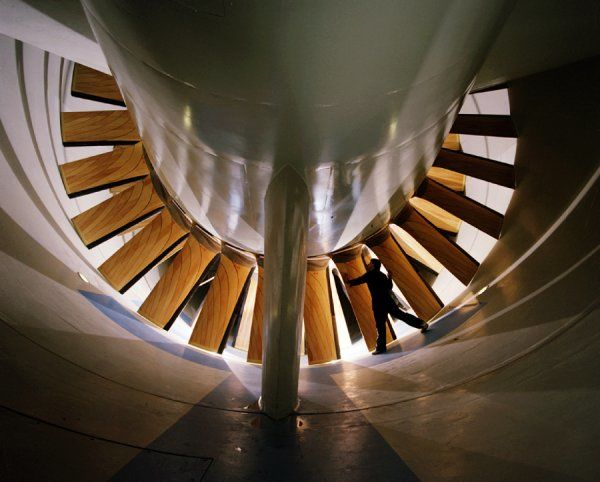 Transonic tunnel fan blades, with light reflections. Grady McCoy is shown standing next to the fan blades