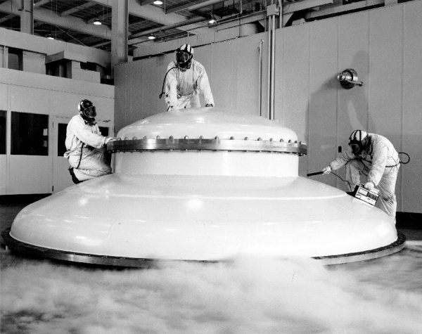 No, it's not a flying saucer, it is the domed top to a 70 foot long vacuum tank at the Lewis Research Center's Electric Propulsion Laboratory, Cleveland, Ohio