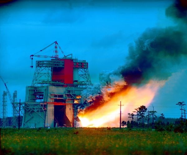 Smoke and flames belch from the huge S-1C test stand as the first stage booster of the Apollo/Saturn V space vehicle is static fired at the NASA Mississippi Test Facility (MTF), currently called Stennis Space Center